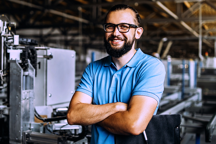 male engineer crossing arms smiling at camera in workshop