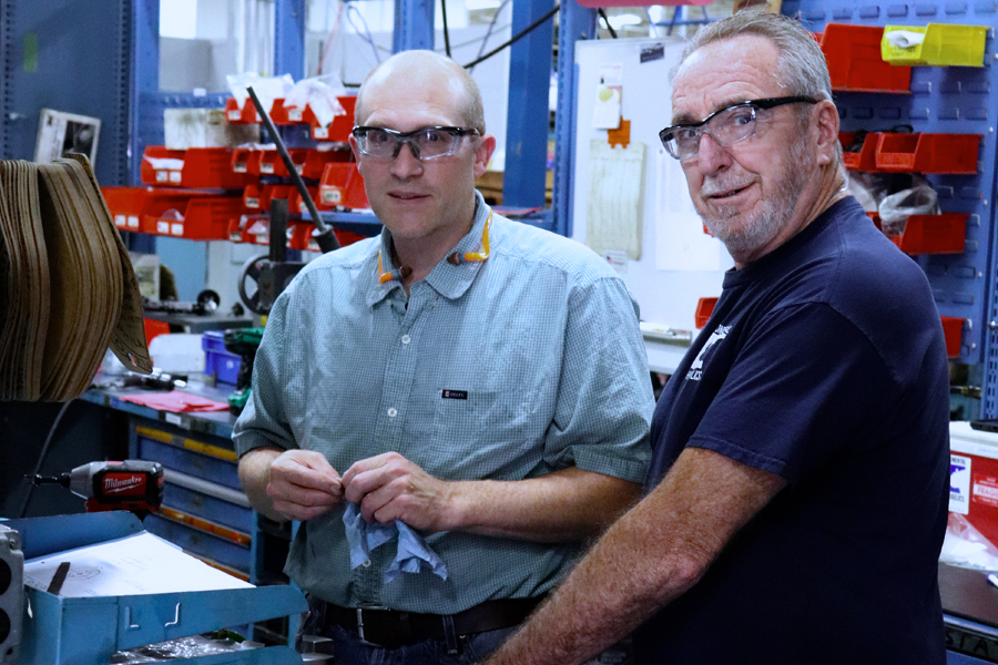 Two engineers smiling at camera in workshop