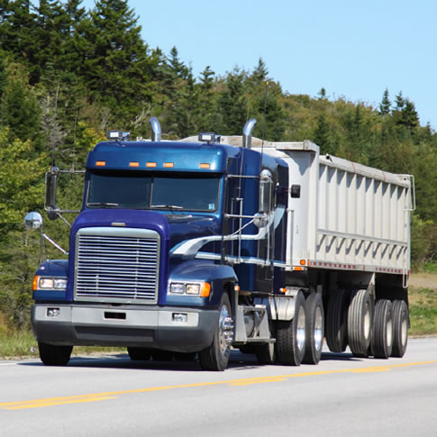 image of big rig on highway; forest background